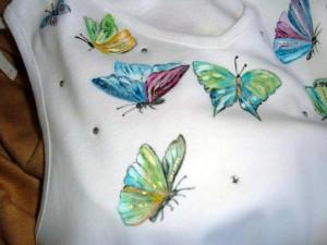 Particolare della maglia dipinta a mano con motivo di farfalle